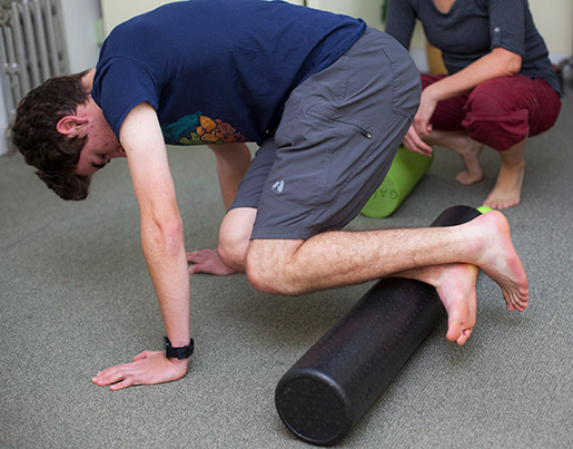 Teen client learning how to use a foam roller for self-care